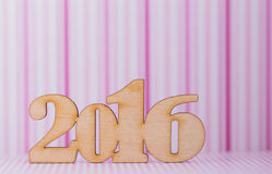 Houten inschrijving van het jaar van 2016 op roze gestreepte achtergrond Royalty-vrije Stock Afbeelding
