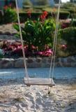 Houten kabelschommeling boven het zand tegen het bloembed Stock Foto