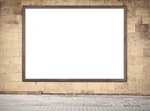 Houten kader met exemplaar het ruimte hangen op grijze bakstenen muur dichtbij de straat Stock Foto's