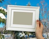 Houten kader in vrouwenhanden achtergrond van het de Winterlandschap met sneeuw Royalty-vrije Stock Foto