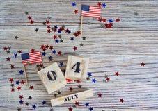 Houten kalender met de datum van 4 Juli, gelukkige onafhankelijkheidsdag, patriottisme en geheugen van veteranen stock foto's