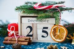 Houten kalender met 25 December-datum daarin op groen onderleggertje, kaars, spar, droge sinaasappelen, pijnbomen De Viering van  stock afbeelding