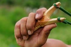 Houten katapultkatapult en handen Stock Afbeelding