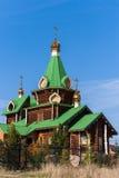 Houten kerk met groene daken en gouden koepels op de blauwe hemelbedelaars Stock Afbeelding