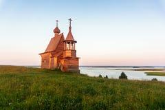 Houten kerk op de bovenkant van de heuvel De zonsondergangmening van het Vershininodorp Arkhangelskgebied, Noordelijk Rusland Stock Afbeelding