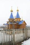 Houten kerk in Siberisch dorp stock afbeeldingen