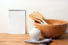 Houten kom en bestek met een notitieboekje op houten achtergrond of lijst Het natuurlijke dienende lijst plaatsen stock foto