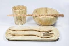 Houten kom en glas en lepel en vork en eetstokjes en schotel Royalty-vrije Stock Afbeeldingen