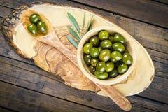 Houten kom en lepel met groene olijven en olijfolie Royalty-vrije Stock Foto's