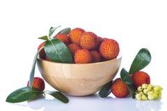 Houten kom met de vruchten van arbutusunedo stock fotografie