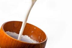 Kom met melk het gieten Stock Fotografie