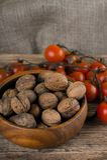 Houten komhoogtepunt van okkernoten en tak van tomaten Stock Fotografie