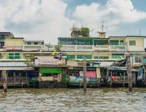 Houten krottenwijken op stelten op de rivieroever van Chao Praya River Royalty-vrije Stock Afbeeldingen
