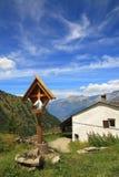 Houten kruis dichtbij landelijk huis in Alpen. Royalty-vrije Stock Afbeelding