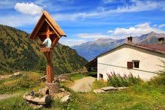 Houten kruis dichtbij landelijk huis in Alpen. Stock Foto's