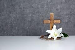 Houten kruis, kroon van doornen en bloesemlelie op lijst tegen kleurenachtergrond stock foto