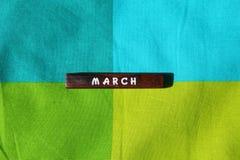 Houten kubus met de naam van de maand maart stock foto's