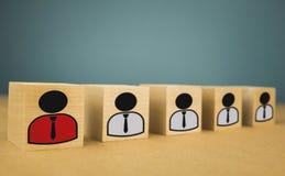 houten kubussen in de vorm van werkgevers en ondergeschikten, personeelsondergeschiktheid op een blauwe achtergrond stock foto's