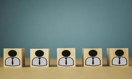 houten kubussen die, loonarbeiders zich op een rij bevinden die betekenen die zich in ??n lijn, abstractie op een blauwe achtergr stock foto