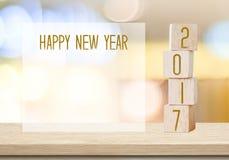 Houten kubussen met 2017 en gelukkig nieuw jaar over onduidelijk beeld bokeh backgr Stock Foto