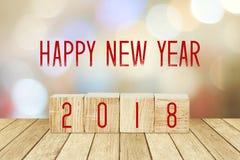Houten kubussen met 2018 en gelukkig nieuw jaar over onduidelijk beeld bokeh backgr Stock Afbeeldingen