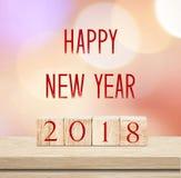 Houten kubussen met 2018 en gelukkig nieuw jaar over onduidelijk beeld bokeh backgr Royalty-vrije Stock Foto