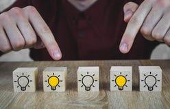 Houten kubussen met het beeld van een gloeilamp die een nieuw idee, concepten innovatie en oplossingen symboliseert, 2 waarvan a  royalty-vrije stock fotografie