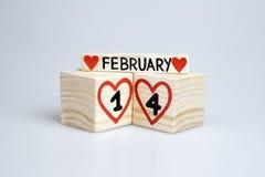 Houten kubussen met met de hand geschreven en vier, rode harten, Februari Stock Afbeelding