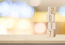 Houten kubussen met 2017 op lijst over nieuwe onduidelijk beeld bokeh achtergrond, Stock Foto
