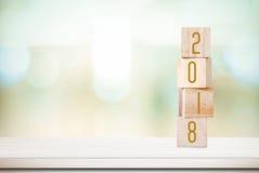 Houten kubussen met 2018 op lijst over onduidelijk beeld bokeh achtergrond met Stock Foto