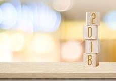 Houten kubussen met 2018 op lijst over onduidelijk beeld bokeh achtergrond met Stock Foto's