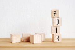 Houten kubussen met 2018 op perspectiefhout over lijst en wit Royalty-vrije Stock Afbeeldingen