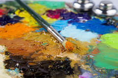 Houten kunstpalet met vlekken van verf en een borstel op witte achtergrond stock afbeelding