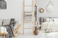 Houten ladder met deken tussen elegante sofa met gevormd algemeen en comfortabel bed met lichtgrijs beddegoed stock afbeeldingen