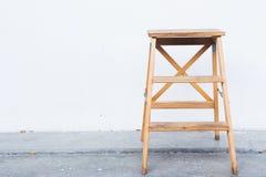 Houten ladder op witte muur met uitstekende houten vloer stock afbeelding