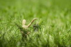 Houten ledenpop met in hand emmer, gevuld met groen gras stock foto