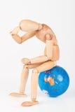 Houten ledenpopzitting bovenop een te beschermen wereldbol isolat Stock Foto
