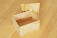 Houten lege doos met deksel die zich naast het op houten vloerachtergrond bevinden stock foto