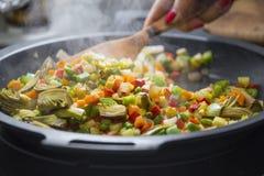 Houten lepel die veggies zich op een pan mengen Stock Afbeelding