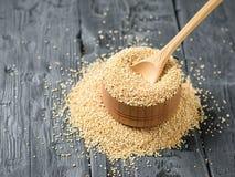 Houten lepel in een kom met quinoa zaden op een donkere houten lijst De mening vanaf de bovenkant stock foto