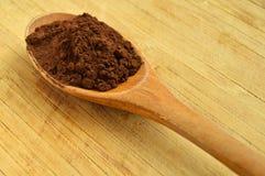 Houten lepel en cacaopoeder Stock Afbeeldingen