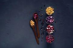 Houten lepel en diverse bonen in metaalkoppen en Spaanse peperpeper, concept gezond vegetarisch voedsel Mening van hierboven Royalty-vrije Stock Afbeelding