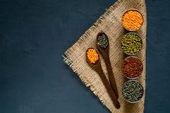 Houten lepel en diverse graangewassen in metaalkoppen, het concept het gezonde eten Hoogste mening Rustieke donkerblauwe achtergr Stock Afbeeldingen