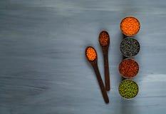 Houten lepel en diverse graangewassen in metaalkoppen, het concept het gezonde eten Hoogste mening Rustieke witte achtergrond Stock Foto