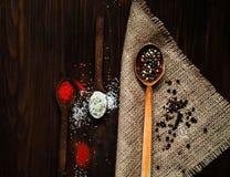Houten lepel en ingrediënten op een donkere achtergrond Het concept kruidig voedsel of culinaire ketchup, hoogste mening, lege ru Stock Afbeeldingen