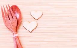 Houten lepel en vork met houten vorm van hart Stock Fotografie