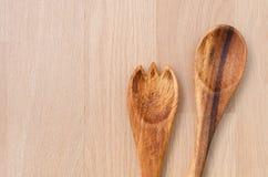 Houten lepel en vork op houten lijstachtergrond Royalty-vrije Stock Foto's