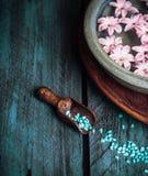 Houten lepel met blauw overzees zout en kom met water en bloemen Royalty-vrije Stock Foto's