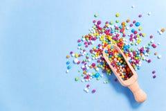 Houten lepel met gekleurd suikergoed, kleurrijke eetbare suikerparels Stock Afbeeldingen