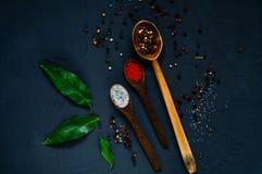 Houten lepels en ingrediënten op een donkere achtergrond Concept kruidig voedsel of het koken, hoogste mening, lege ruimte voor t Stock Foto's